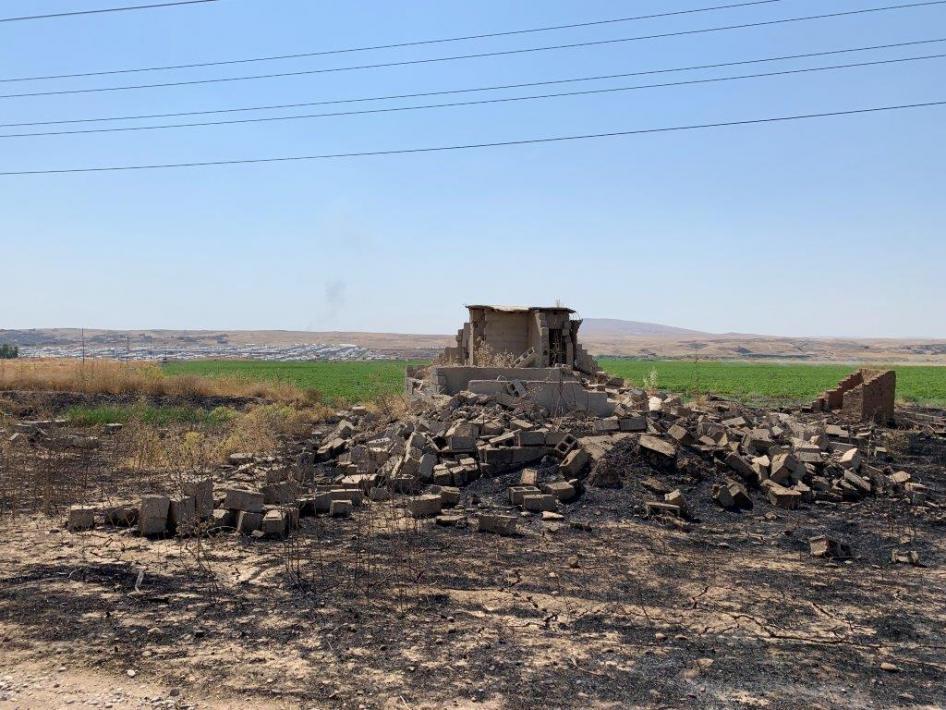 منزل مدمّر قرب قرية أش قلعة الصغير في الحمدانية، يوليو/تموز 2019. يظهر مخيّم حسن شامي في الخلفية.  © بلقيس والي/هيومن رايتس ووتش.